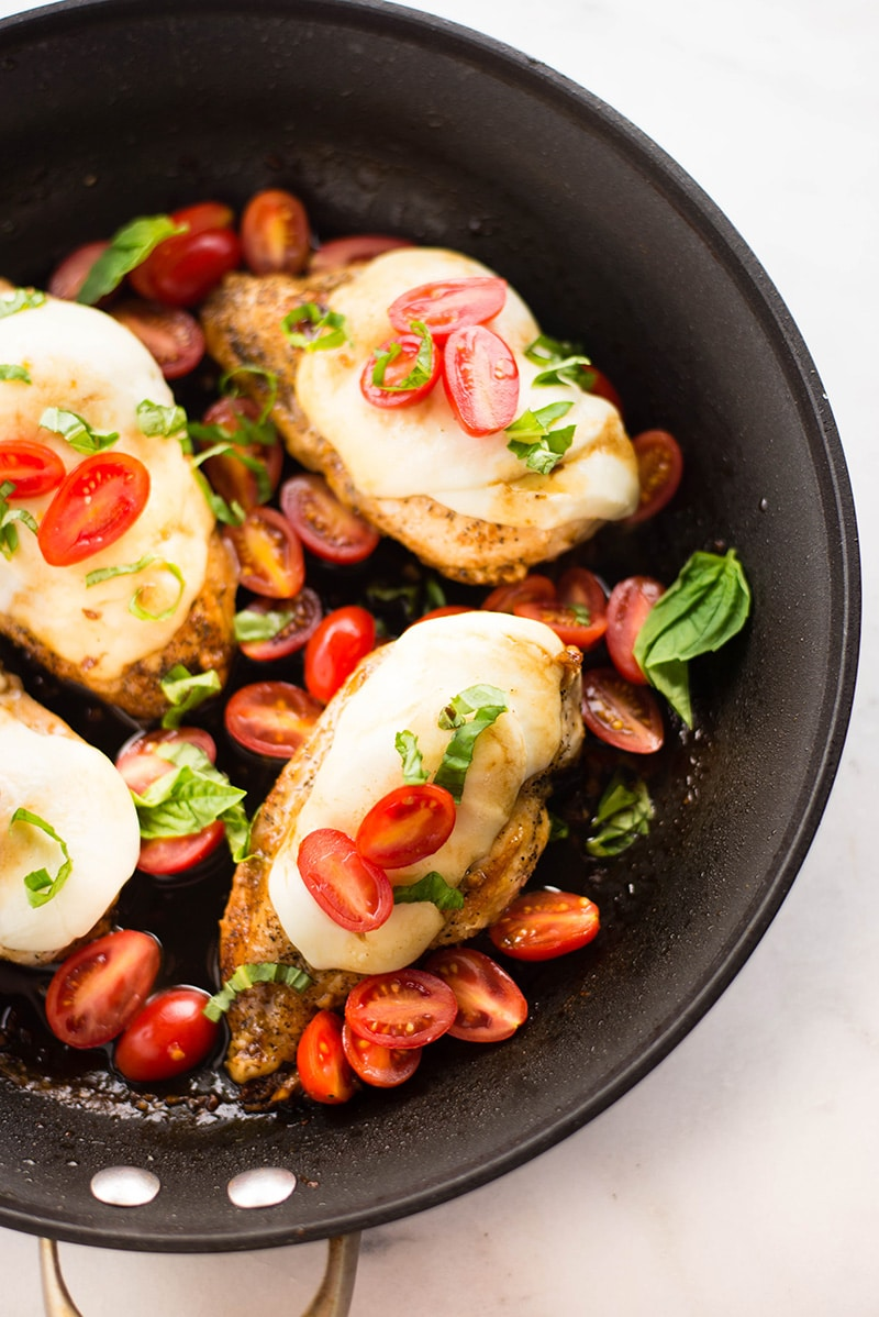 Close up of the skillet filled with the one pan chicken bruschetta. Can see the chicken topped with mozzarella, grape tomatoes, and fresh basil.