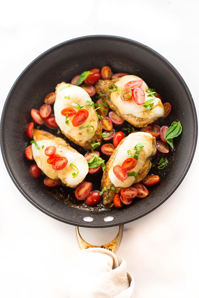 Overhead view of a skillet with four boneless skinless chicken breasts topped with fresh sliced mozzarella cheese, sliced tomatoes, and fresh basil and in a balsamic sauce.