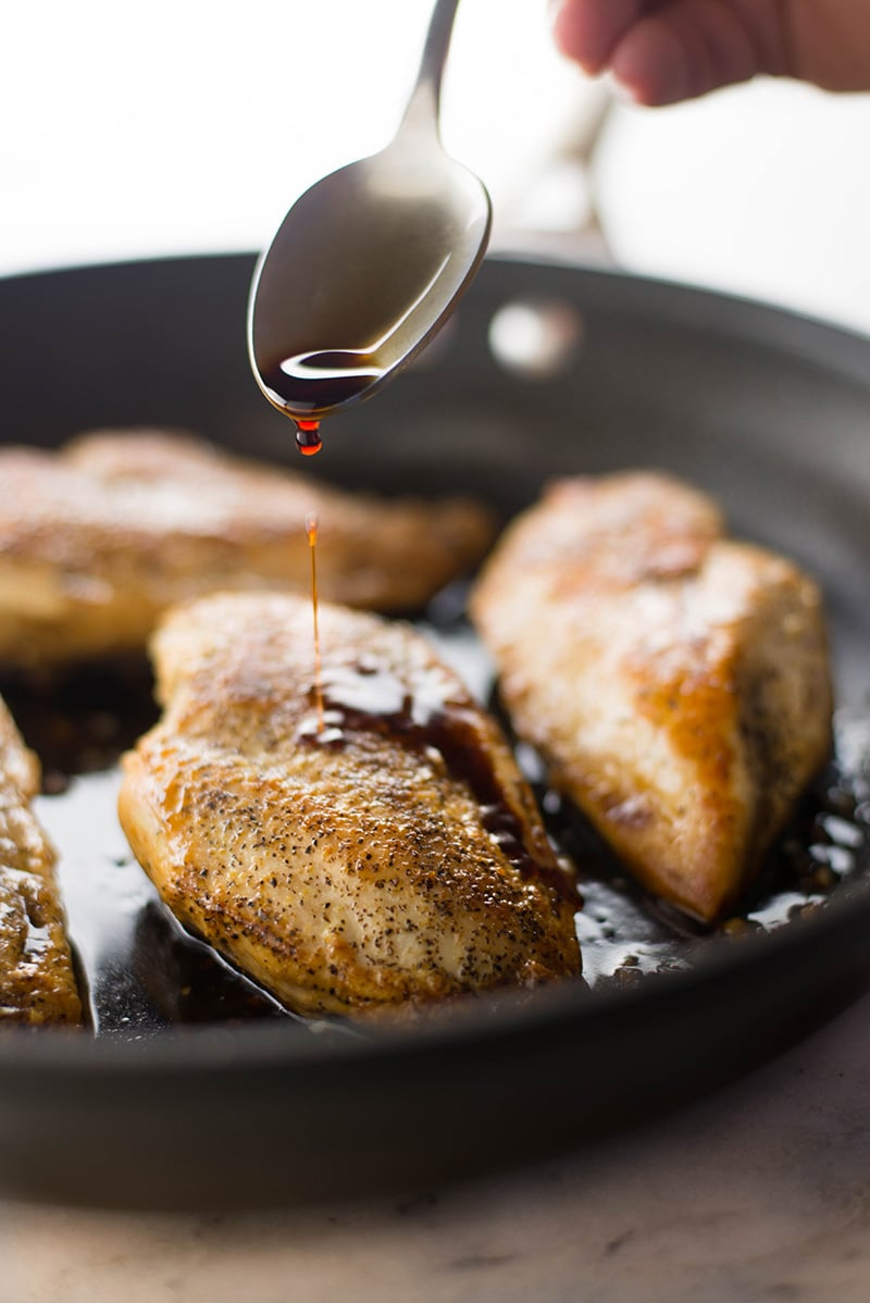 Side view of a spoon drizzling the balsamic sauce over the chicken in the skillet for the chicken bruschetta.