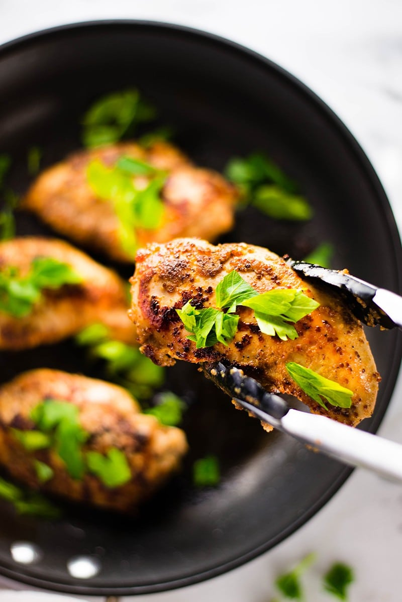 Close up of honey mustard chicken, garnished with chopped Italian parsley and ready to be served
