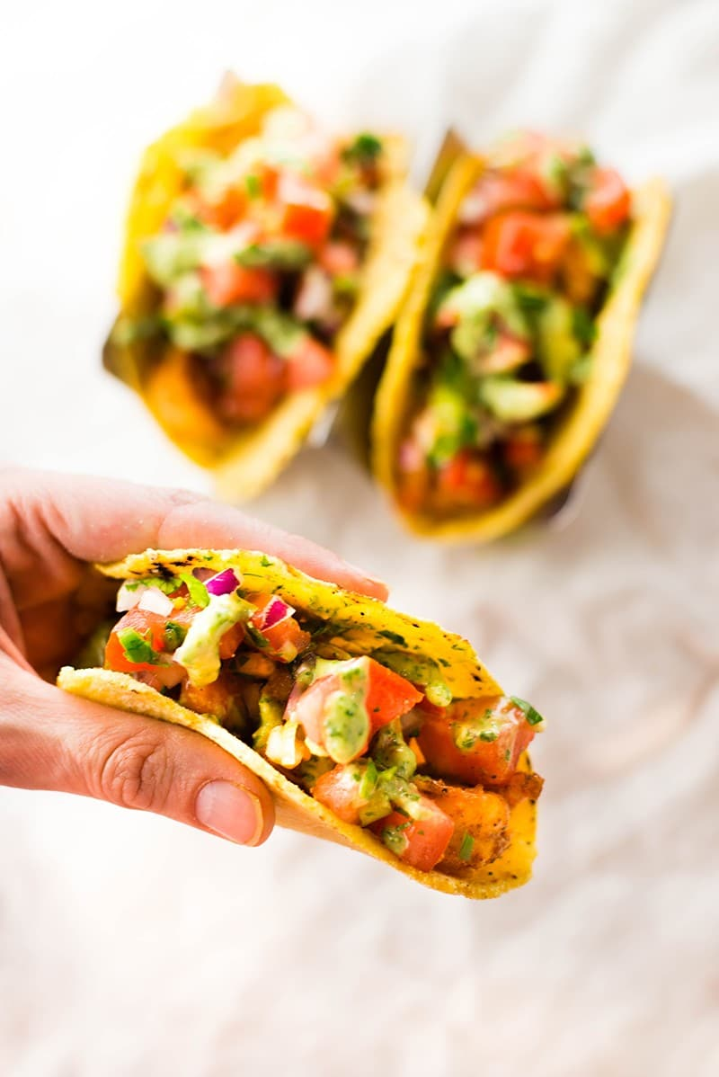 Close up of spicy shrimp tacos, topped with Pico de Gallo and avocado cilantro lime sauce, ready to be enjoyed