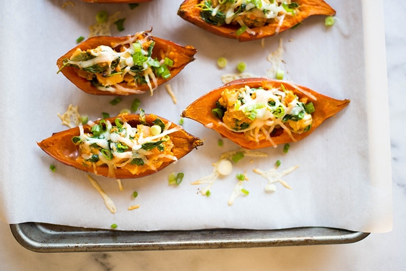 Horizontal view of the baked sweet potato skins that have been filled with cooked chicken, greek yogurt, spinach, onion, and sweet potato puree.
