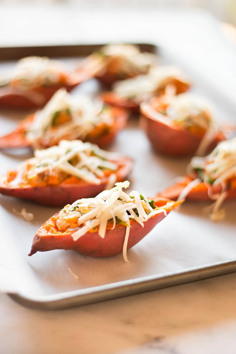 Rimmed baking sheet with unbaked sweet potato skins that have been stuffed with spinach and topped with shredded cheese.