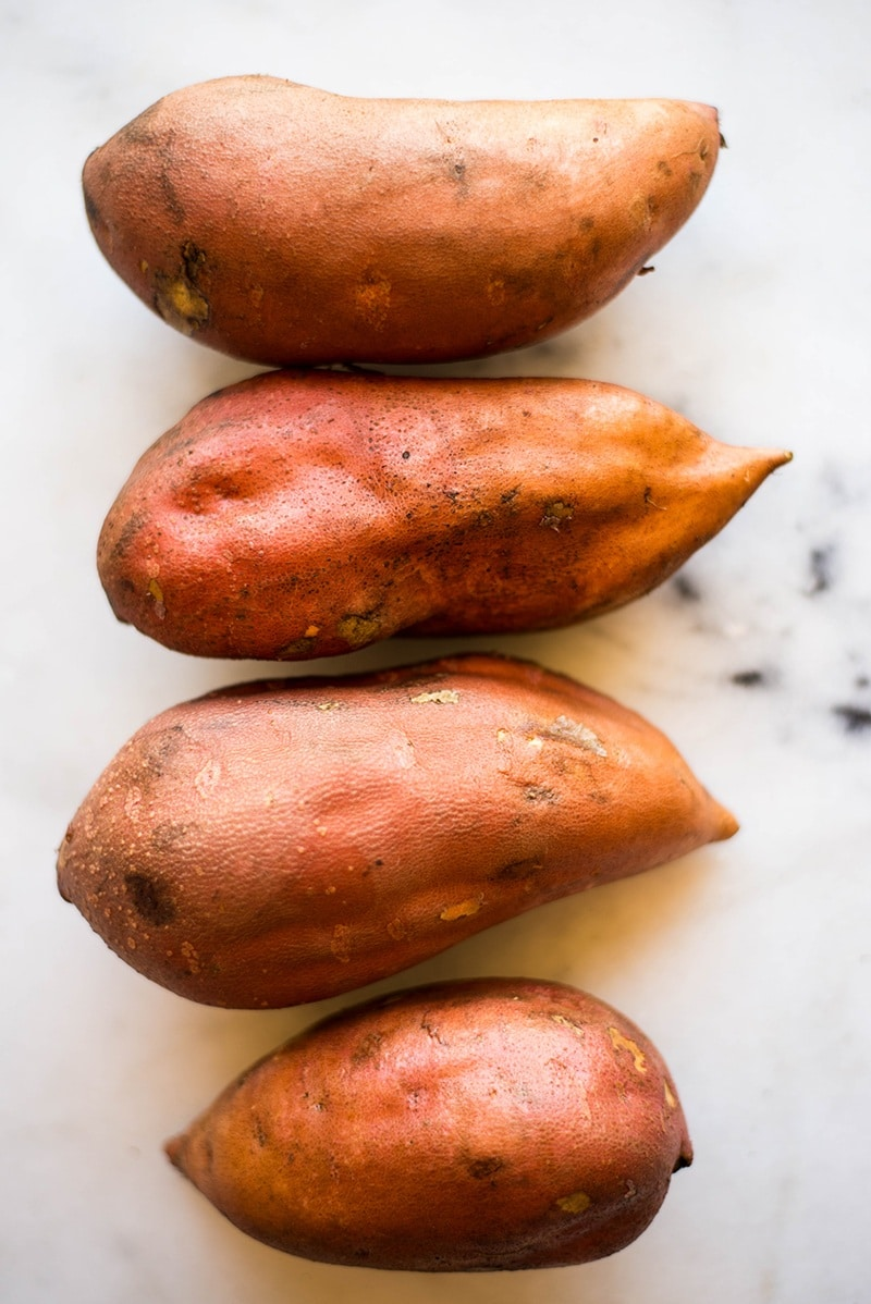 Four uncooked sweet potatoes in a row that have skin on them, ready to be baked for sweet potato skins.