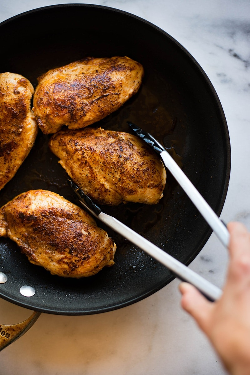Seasoned chicken breasts grilling in a skillet, ready to be shredded and used as topping for the sweet potato nachos.