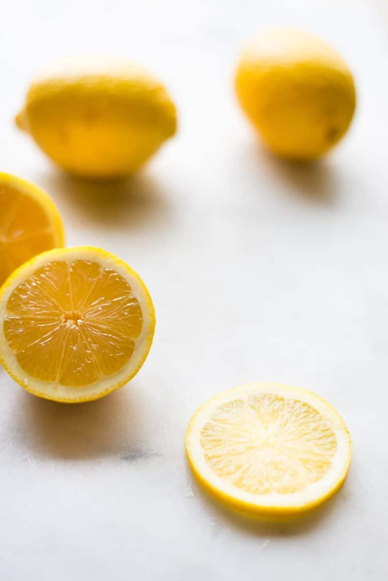 Closeup image of two whole lemons, a lemon cut in half, and a slice of lemon.