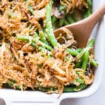 Overhead view of Healthy Green Bean Casserole in white baking dish with wooden spoon ready to serve.
