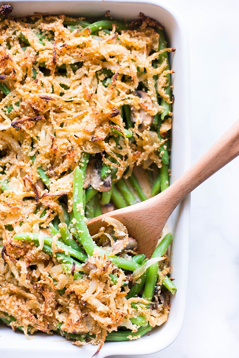 A wooden spoon getting some of the homemade healthy green bean casserole that is topped with crispy onions that are coated in almond meal and ready to enjoy as a healthy Thanksgiving side.