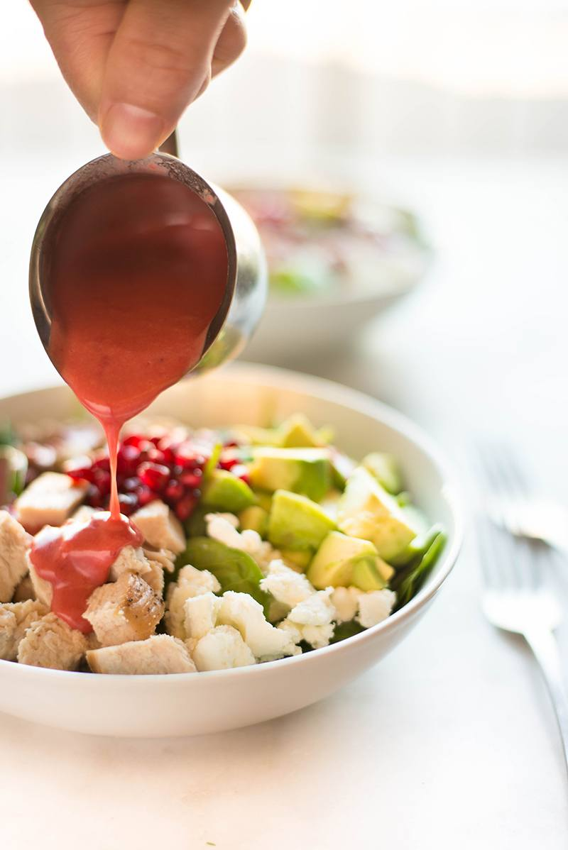 Drizzling the fresh cranberry vinaigrette over the leftover turkey salad, ready to eat.