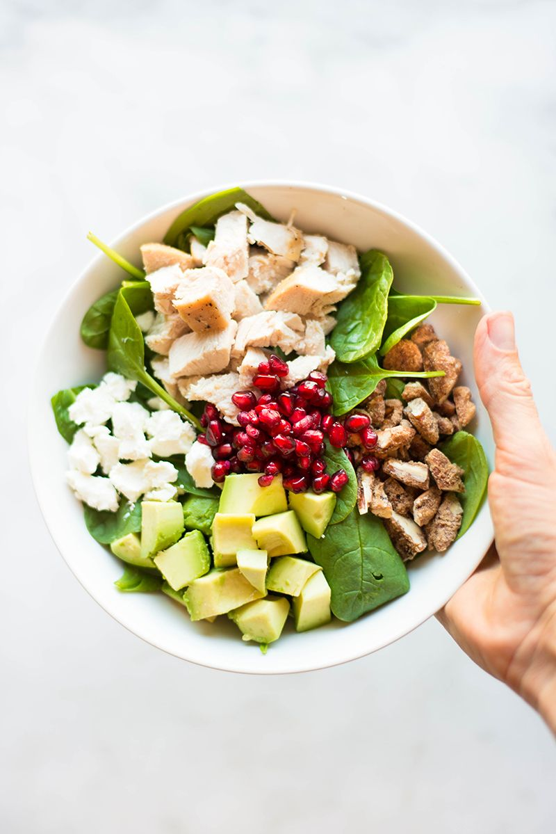 One hand holding a bowl of the leftover turkey salad, which contains goat cheese, avocado, pomegranate seeds, leftover thanksgiving turkey, baby spinach, and candied pecans.
