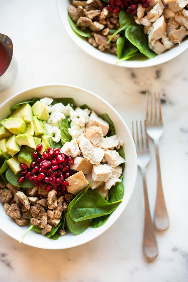 Overhead shot of two bowls of the leftover turkey salad ready to be drizzled with the fresh cranberry vinaigrette. In the salad, you can see the fresh baby spinach, diced avocado, candied pecans, diced leftover turkey, and pomegranate seeds.