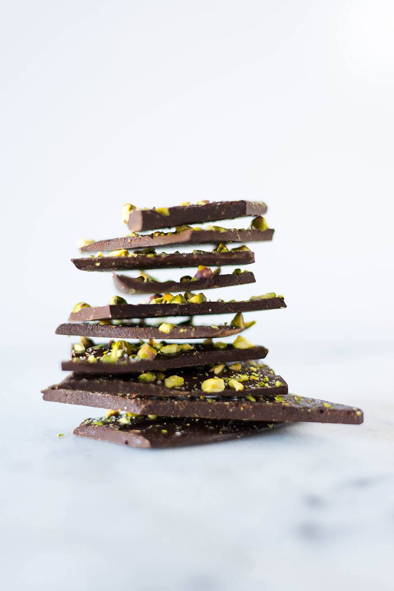 Side view of a stack of Pistachio Dark Chocolate Bark, a healthy treat and a good way to eat dark chocolate for benefits.