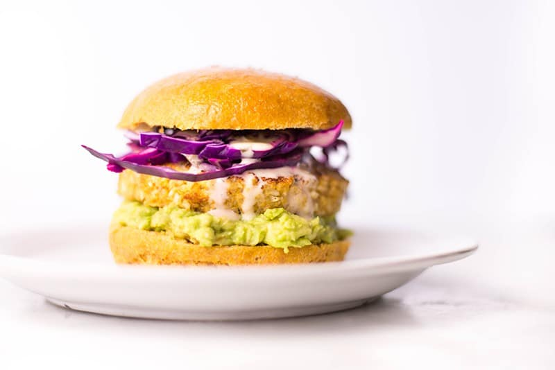 Side of view of the Spicy Cauliflower Quinoa Ranch Burger With Sweet Potato Bun, garnished with red onion and avocado.