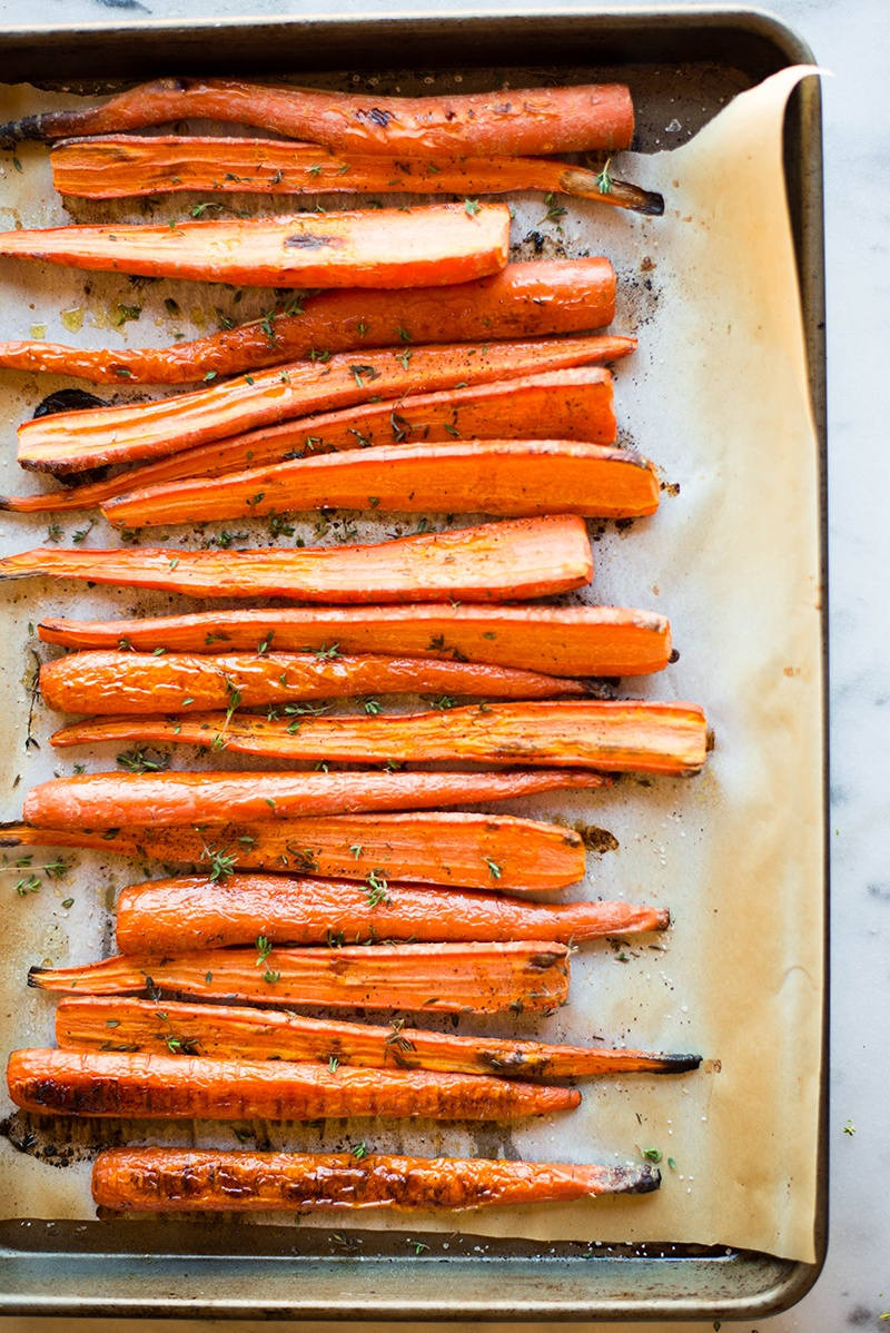 Overhead image of a sheet pan lined with ready to serve Thyme-Roasted Carrots.
