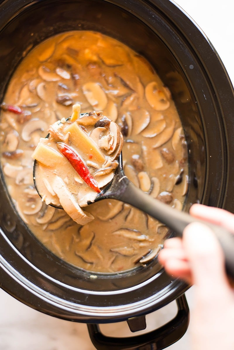 Overhead image of a spoon of the slow cooker hot and sour soup with thinly sliced shiitake mushrooms, cremini mushrooms, extra firm tofu and a dried red chili pepper over a slow cooker