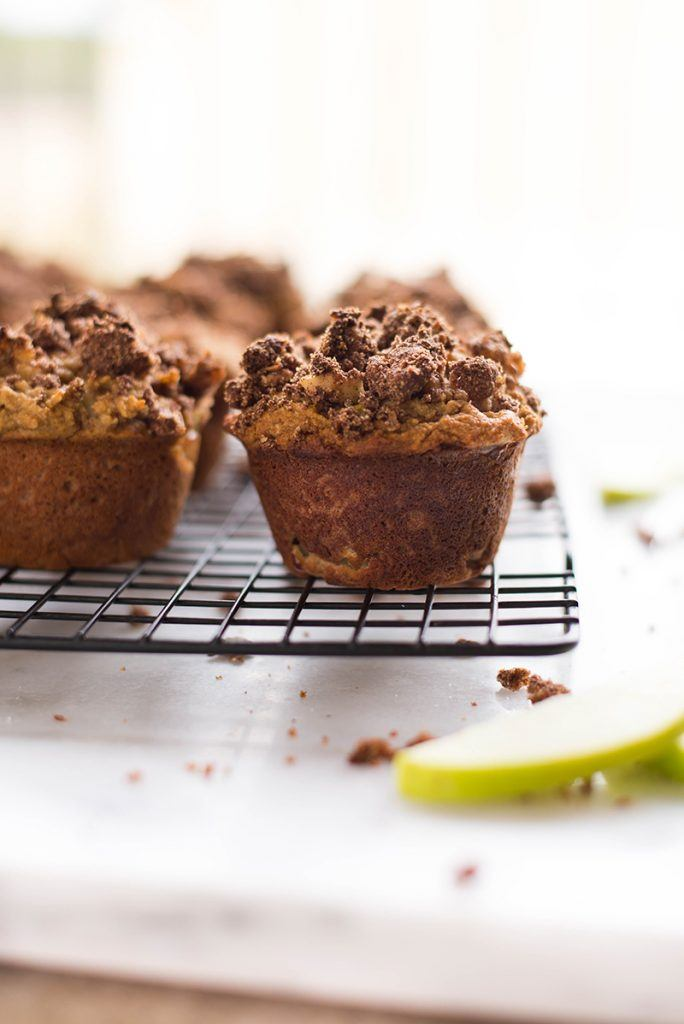 Side view of Paleo Apple Crunch Muffins with a crumbly topping sitting on a cooling rack, waiting to be eaten as a Healthy Breakfast Idea.