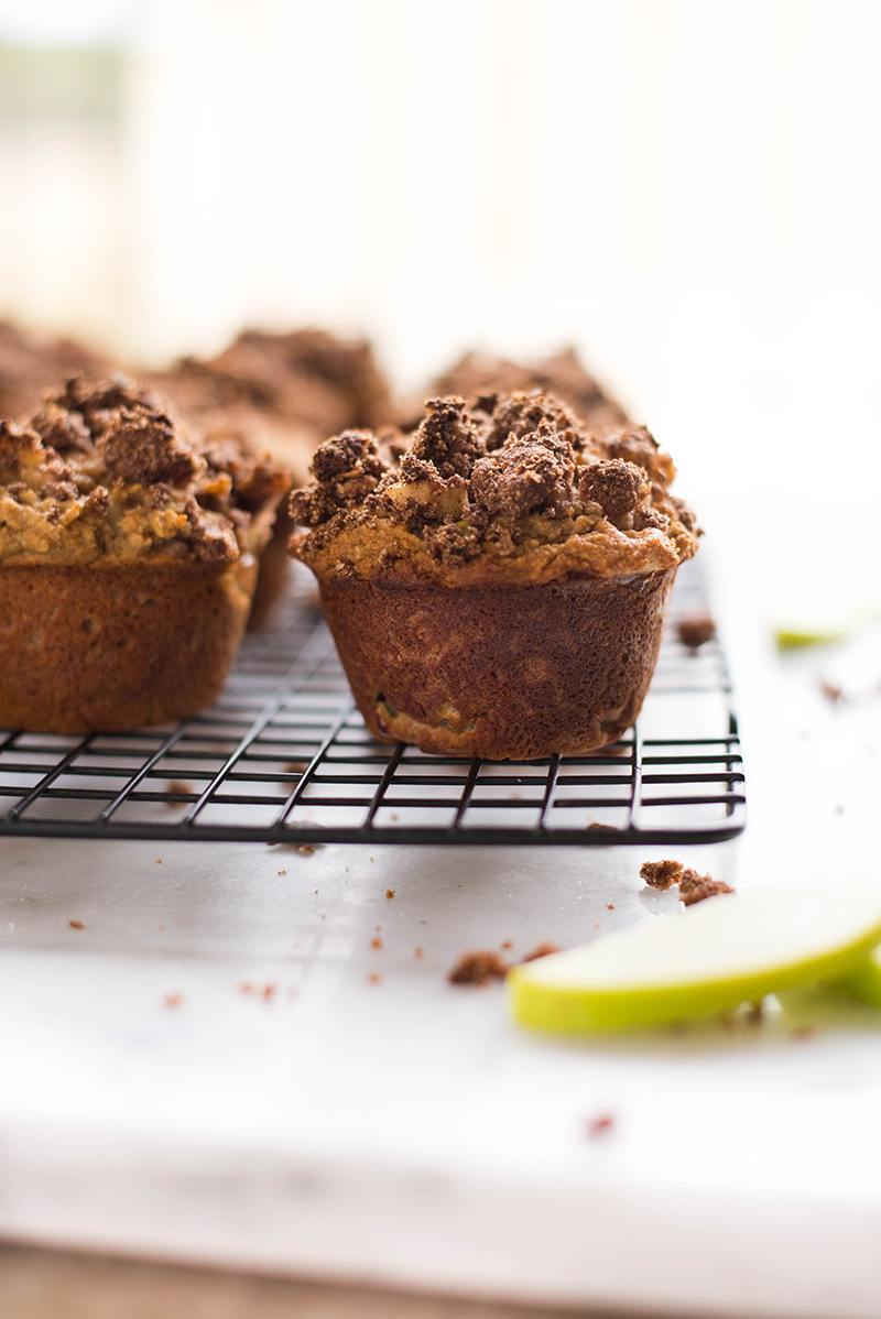 Close up image of a cooling tray with freshly baked Paleo Apple Crunch Muffins, with slices of green apple beside it.
