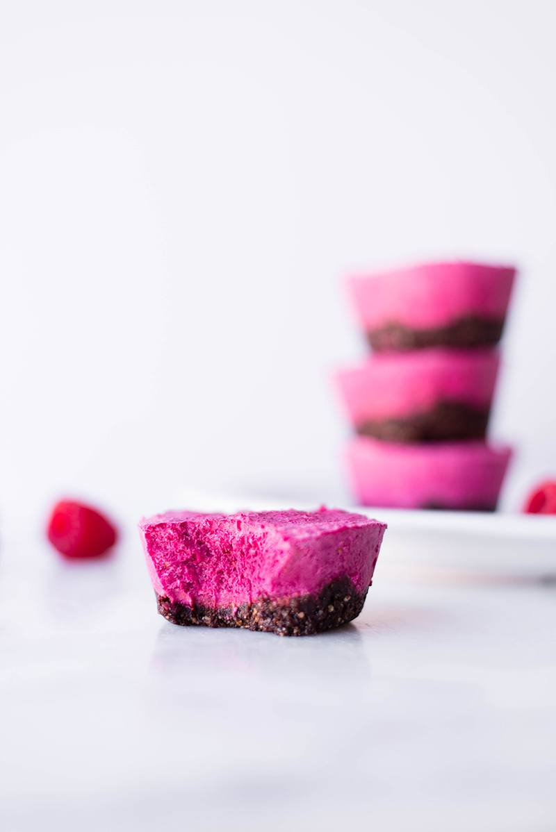 Up close of one of the raspberry beet mini cheesecakes that has been bitten into to show the inside texture of the mini cheesecake. In the background are more no bake mini cheesecakes and fresh raspberries.