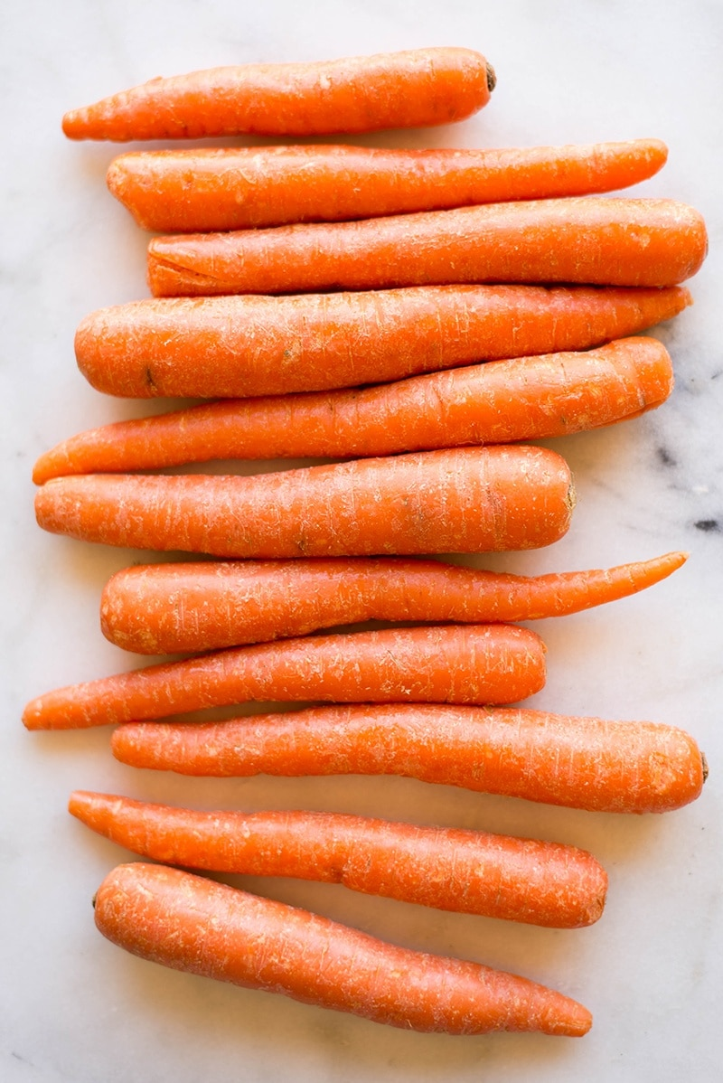 Raw whole carrots, ready to be peeled and sliced to make baked carrot fries