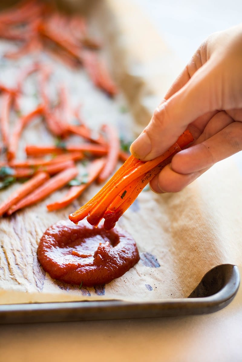 Baked carrot fries dipped into homemade ketchup without sugar and ready to be enjoyed