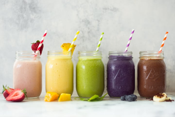 Close up image of 5 high protein smoothies in mason jars with striped straws, 2 of which do not contain bananas for the banana free smoothies.