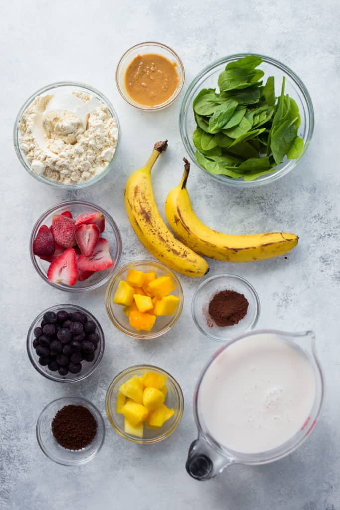 Overhead image of ingredients for high protein fruit smoothie recipes for weight loss, including bananas, vanilla protein powder, baby spinach, strawberries, blueberries, and mangoes.