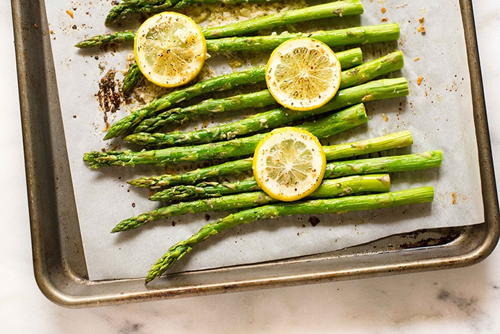 Close-Up of Asparagus topped with Parmesan Cheese on a Cookie Sheet Covered Pan After Roasting