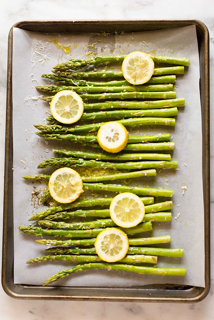 Asparagus topped with Parmesan Cheese and Lemon on a Cookie Sheet Covered Pan Pre-Oven
