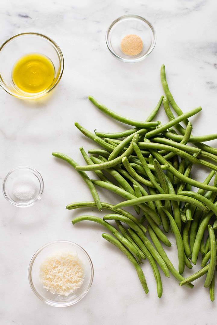Fresh green beans placed next to bowls of olive oil, garlic powder, grated Parmesan, and sea salt, to be used for Parmesan roasted green beans recipe
