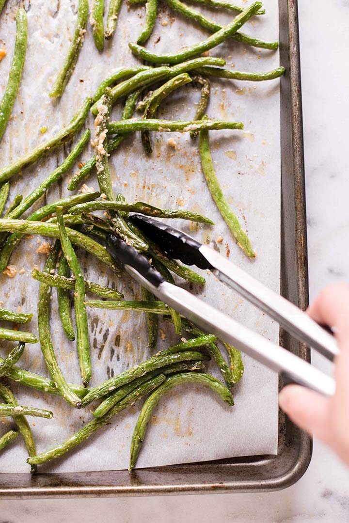 : Parmesan roasted green beans on a baking tray, ready to be plated and served