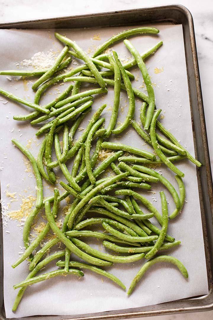 Seasoned fresh green beans, ready to be baked in the oven to make Parmesan roasted green beans