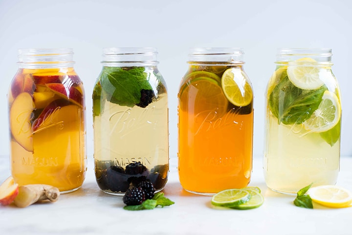 Four quart sized mason jars, steeping with the iced tea and various flavors