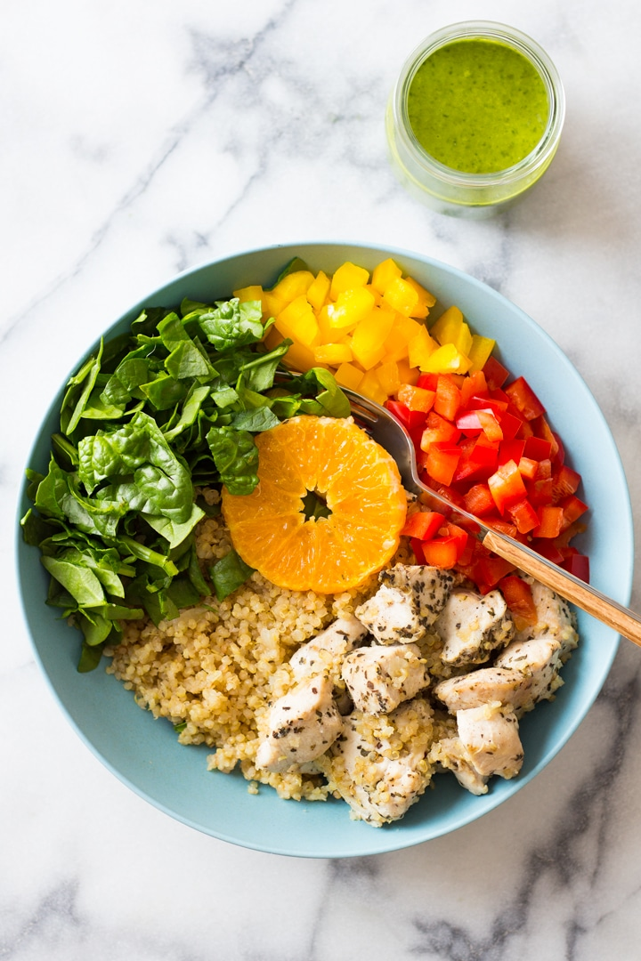 Overhead image of a blue bowl with quinoa, peppers, chicken, and spinach ready to eat. There is a green smoothie beside the bowl.
