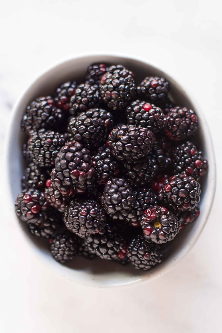 Bowl of fresh blackberries in a white bowl.