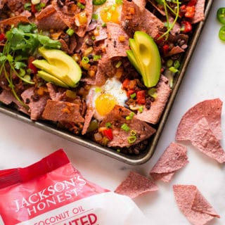 Overhead view of the baked healthy sheet pan breakfast nachos next to bag of opened Jackson's Honest Sprouted Red Corn Tortilla Chips, Ready To Eat.