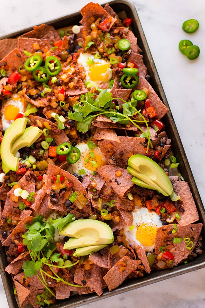 View of Healthy Sheet Pan Breakfast Nachos with demonized foods that are actually good for you, like avocado, eggs, and veggies.