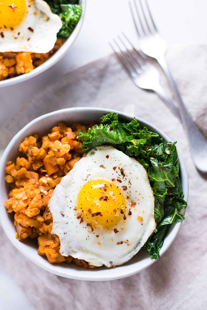Overhead view of two bowls filled with sweet potato and lentil hash, garlic sauteed kale, and topped with fried egg with crushed red pepper flakes and black pepper sprinkled over the top.