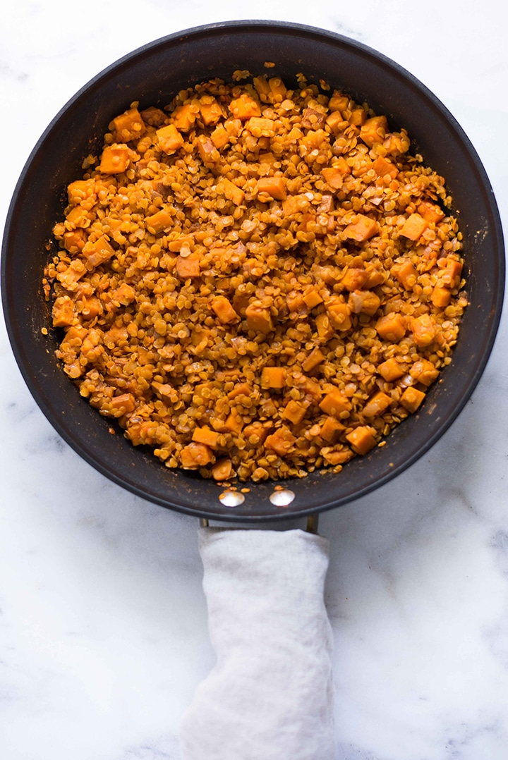 Skillet with cooked red lentils and sweet potatoes, ready to be plated