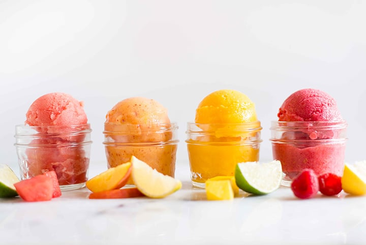 Four 4-oz. mason jars filled with easy sorbet recipes, including watermelon sorbet, peach sorbet, mango sorbet, and raspberry sorbet, ready to eat.