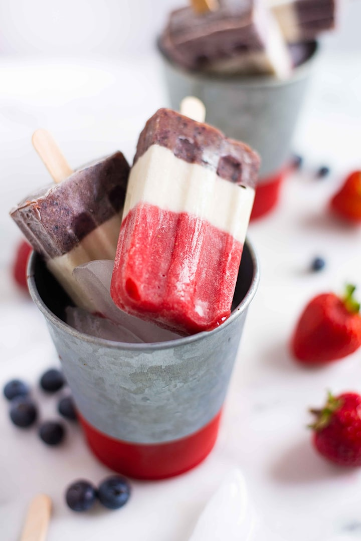 Close up shot of a red white and blue fruit popsicle ready to be eaten that is setting on top a metal can filled with ice to be enjoyed for the 4th of July.