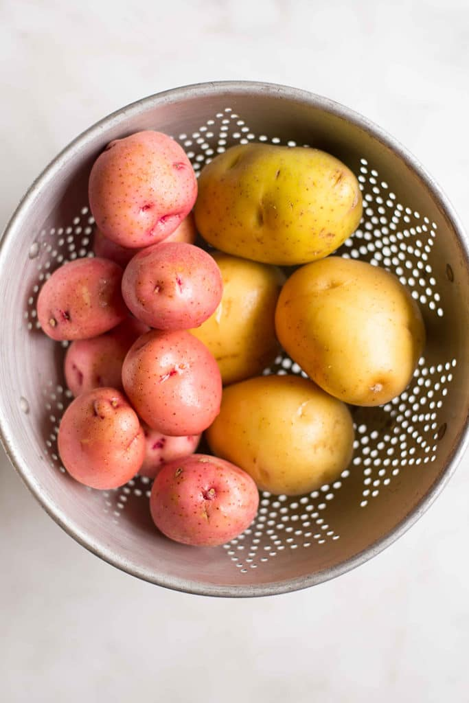 Overhead view of a stainless steel colander containing red and yellow potatoes, washed and with the skin on.