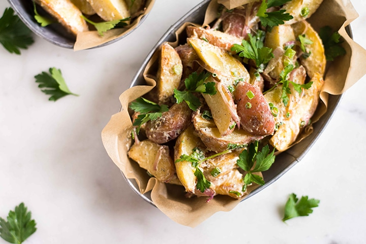 Close up of the roasted potato salad, ready to eat and garnished with fresh Italian parsley.