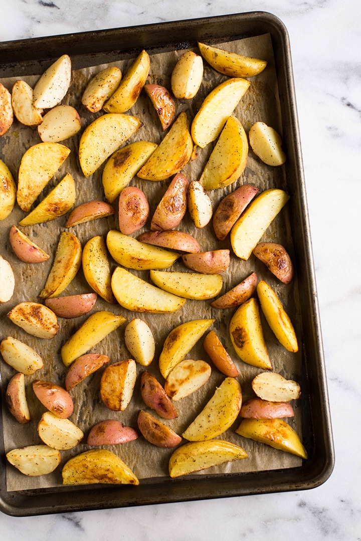 Rimmed baking sheet lined with parchment paper with the seasoned red potatoes and yukon gold potatoes laid out, ready to roast in the oven.