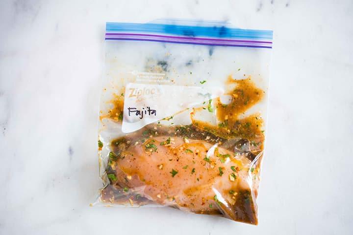 Sealable freezer bag with chicken breast and fajita chicken marinade, marinating and ready to cook.