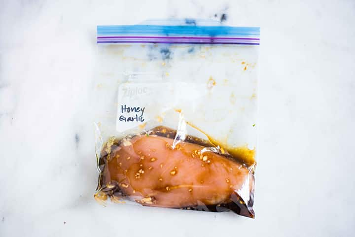 Sealable freezer bag with chicken breast and honey garlic chicken marinade, marinating and ready to cook.