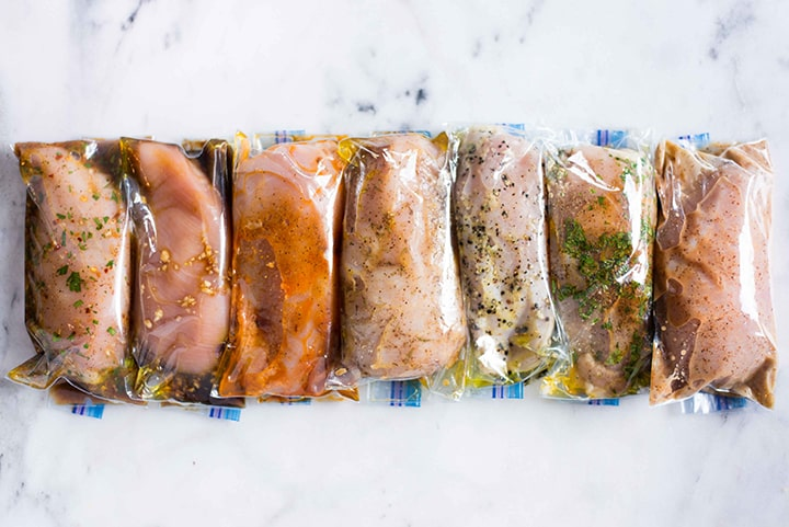 7 sealable freezer bags filled with boneless, skinless chicken breasts and marinating in different chicken marinades, including honey mustard, cilantro lime, lemon pepper, chipotle, honey garlic, jerk, and fajita.
