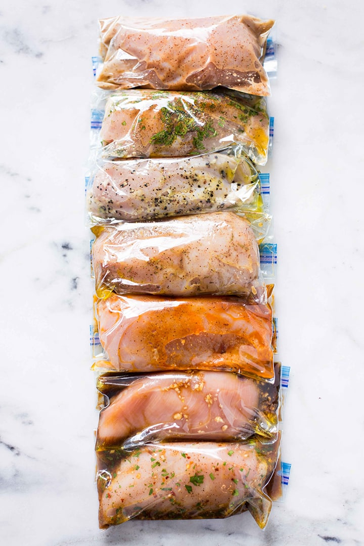 Overhead image of the 7 Best Chicken Marinades covering chicken and placed in freezer ziploc bags.