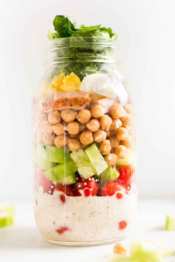 Quart size mason jar filled with protein packed ingredients, including spinach, chickpeas, turkey, hard-boiled egg, and a creamy Italian dressing.
