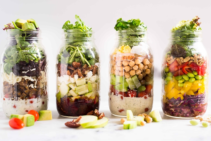 Four quart sized mason jars, each filled with a different salad (beet and gaot cheese, protein packed mason jar salad, asian chopped salad, and taco salad), in a row