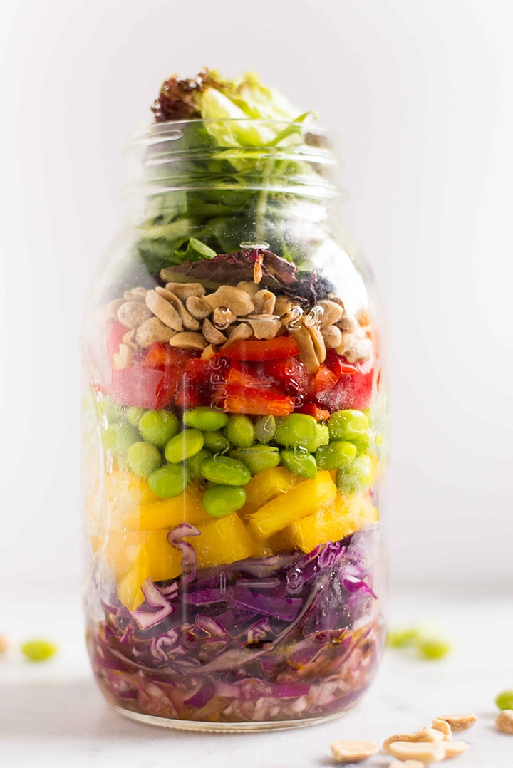Quart size mason jar filled with chopped asian salad with mandarin orange vinaigrette, along with shredded red cabbage, diced yellow bell pepper, shelled edamame, diced red bell pepper, raw peanuts, and mixed baby greens.